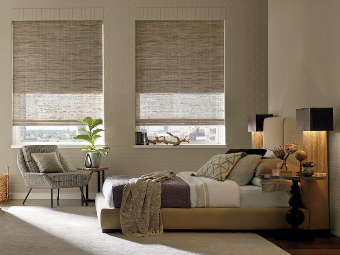 A bedroom with woven wood shades.